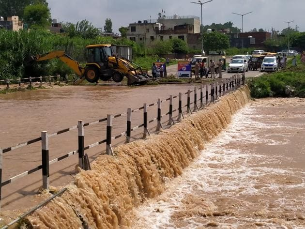 Water flows over a bridge in Chandigarh's Bapudham colony and traffic is held up after heavy weekend showers led to a rise in levels of the Sukhna Lake and streams nearby.(Keshav Singh)
