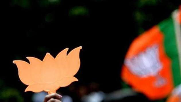 File photo: Supporters of Bhartiya Janta Party (BJP) wave party flags and cut-outs of the lotus.(AFP)