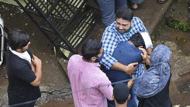 People console each other at the site of the building collapse, in Mahad on Tuesday.(PTI)