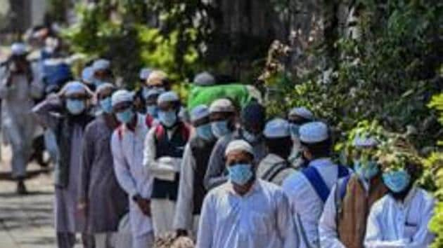 People who took part in a Tablighi Jamaat function earlier this month walk to board buses taking them to a quarantine facility amid concerns of infection, on day 7 of the 21 day nationwide lockdown imposed by PM Narendra Modi to check the spread of coronavirus, at Nizamuddin West in New Delhi.(Biplov Bhuyan/HT PHOTO)