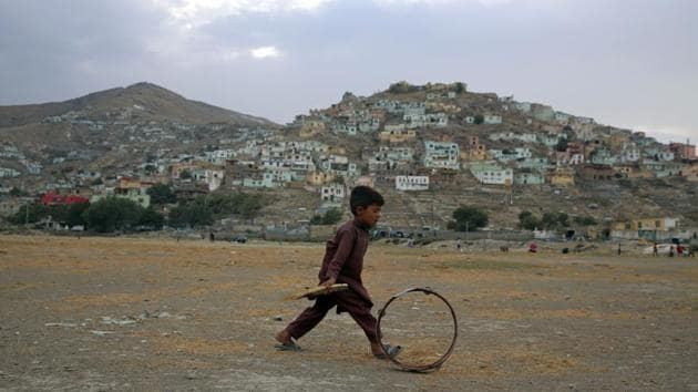 An Afghan boy pushes a wheel on the outskirts of Kabul, Afghanistan.(AP)