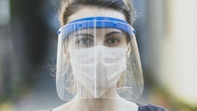 A woman wearing a face mask and a shield.(Unsplash)