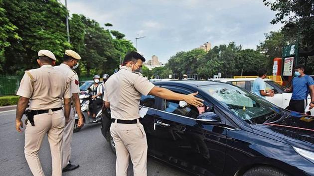 Delhi Police personnel penalizes commuters for violation of Covid-19 protocols at Connaught Place area in New Delhi, India, on Monday, August 24, 2020. (Photo by Raj K Raj/ Hindustan Times)