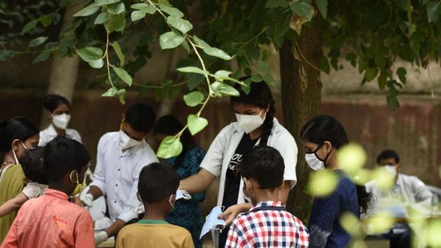 A health worker distributes face masks to children during a coronavirus testing drive, at Ayushman Bharat Health and Wellness Centre, in Gurugram in July. The National Health Authority ) that is the implementing authority of the country's flagship public health insurance scheme --- Ayushman Bharat Pradhan Mantri Jan Arogya Yojna --- has released the draft policy for public comments and feedback until September 3.(Parveen Kumar/HT Photo)