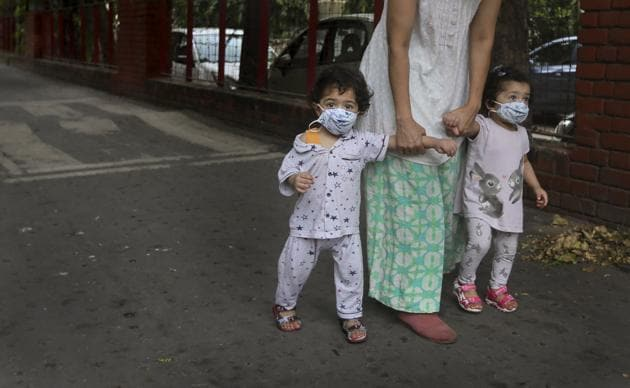 A woman takes her toddlers for a walk, their faces covered with masks as a precaution against the coronavirus, in New Delhi.(AP)