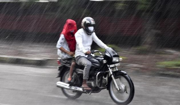 Commuters caught unawares by the rain in Chandigarh on Thursday.(Keshav Singh/HT)