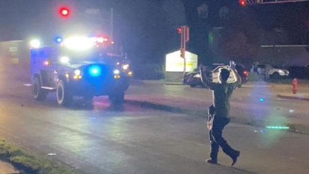 A man with a firearm raises his hands up as he walks towards vehicles during a protest following the police shooting of Jacob Blake, a Black man, in Kenosha, Wisconsin.(Reuters)