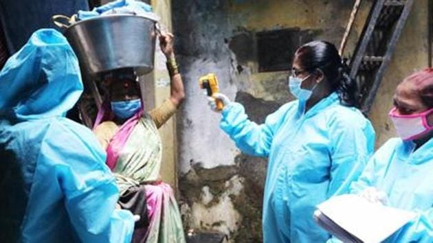 Healthcare workers wearing personal protective equipment (PPE) conduct door to door thermal screening of residents.(ANI)