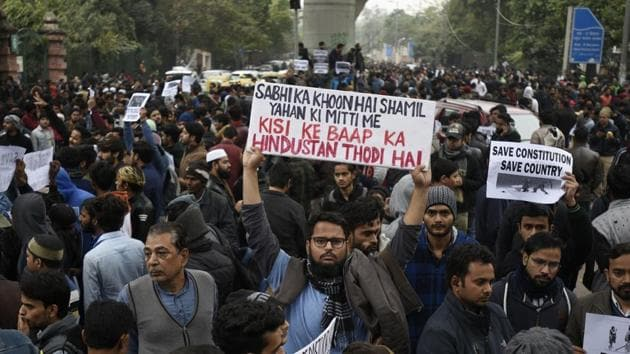 Protesters hold placards against the Citizenship (Amendment) Act outside Jamia Millia Islamia, New Delhi, in December.(HT PHOTO)