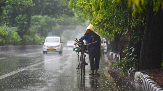New Delhi, India - Aug. 19, 2020: A commuter pushes his cycle under rain near Adchini in New Delhi, India, on Wednesday, August 19, 2020. (Photo by Amal KS/ Hindustan Times)(Amal KS/HT PHOTO)