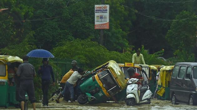 People try to pull an overturned auto rickshaw along a waterlogged road following monsoon rainfalls in New Delhi . The death toll from the torrential monsoon rains across South Asia has risen to nearly 1,300 as Bangladesh experienced its second-worst floods since independence and Nepal reeled from several fatal landslides.(AFP)