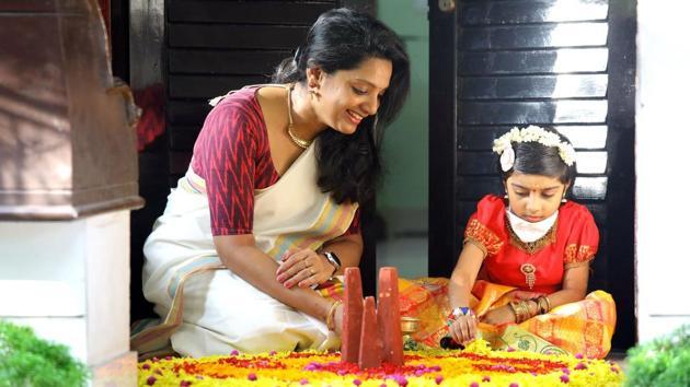 Kerala, India – August 25, 2020: A woman and child making Onam Pookalam (flower rangoli) in Thiruvananthapuram District, Kerala, India.(Vivek R. Nair / Hindustan Times)