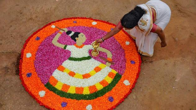 Chikmagalur: A Keralite woman makes 'Pookalam' (flower rangoli) on the occasion of Onam festival, Chikmagalur in Karnataka on Monday.(PTI)