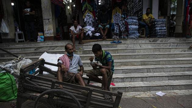 Laborers rest on a pushcart at a market area in Guwahati, India.(AP)