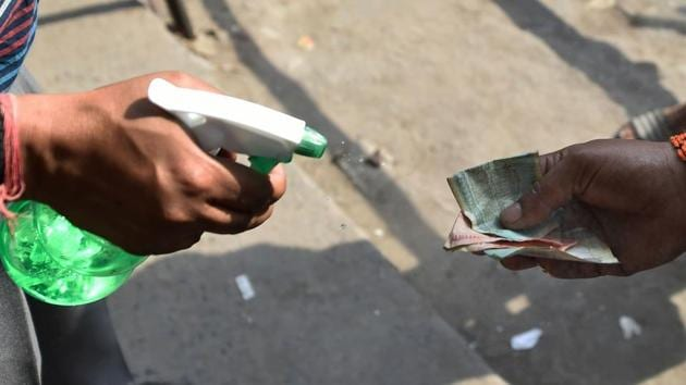 A shopkeeper sprays disinfectant on currency notes of a customer after buying liquor from a wine shop at Chander Nagar in East Delhi.(PTI)