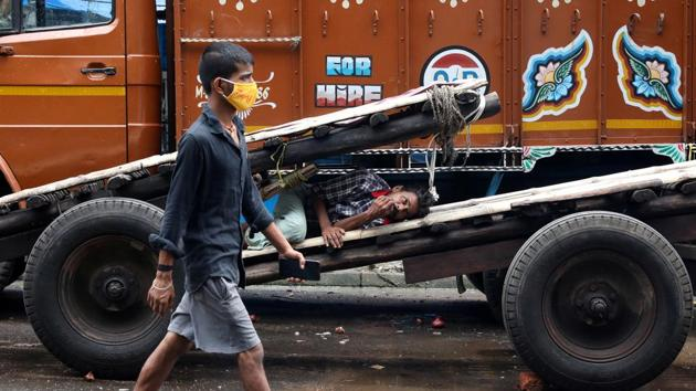 A man wearing a protective face mask walks past a labourer resting on a handcart in a closed wholesale market in West Bengal.(REUTERS)