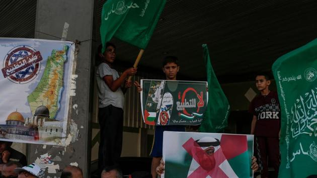 Palestinian demonstrators wave the green flag of the Hamas movement, carry pictures of Abu Dhabi's Crown Prince Sheikh Mohammed bin Zayed Al-Nahyan as well as banners with slogans against a US-brokered deal between Israel and the UAE to normalise relations, during a rally in the northern Gaza Strip refugee camp of Jabalia.(AFP)