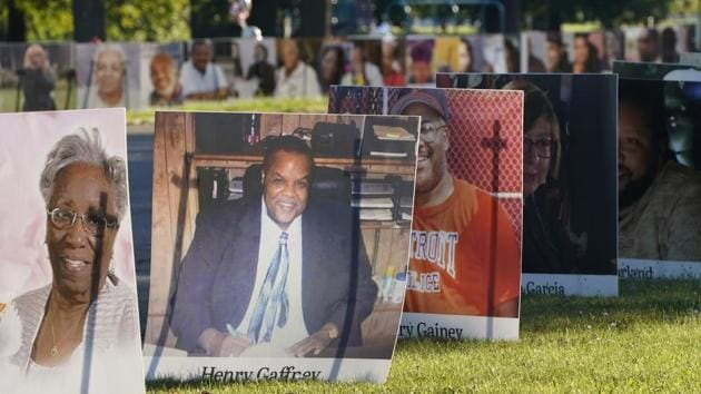 Some of the nearly 900 large poster-sized photos of Detroit victims of COVID-19 are displayed, Monday, Aug. 31, 2020 on Belle Isle in Detroit.(AP Photo/Carlos Osorio)