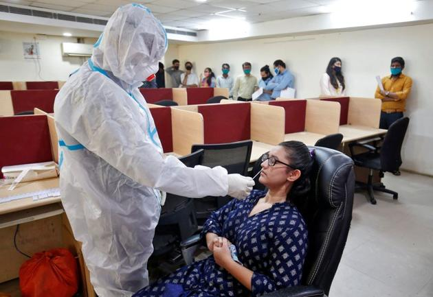 A healthcare worker wearing personal protective equipment (PPE) takes a swab from a woman for a rapid antigen test inside an office, amidst the coronavirus disease (COVID-19) outbreak, in Ahmedabad, India, September 2, 2020. (Representational image)(REUTERS)