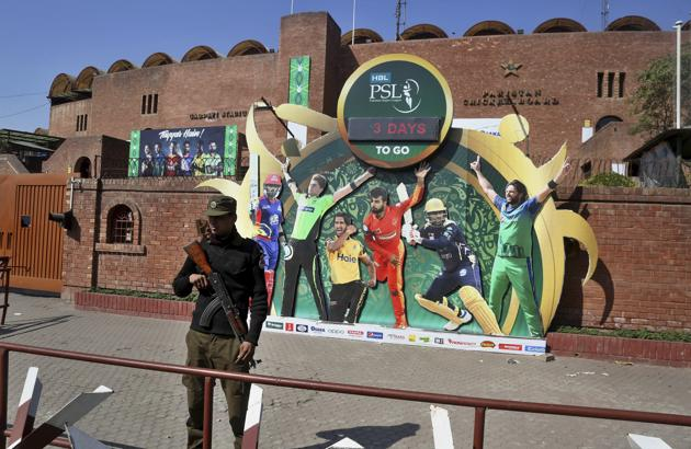 In this Monday, Feb. 17, 2020 photo, a police officer stands guard next to poster of cricket players displayed outside the Gaddafi stadium for upcoming Pakistan Super League, in Lahore, Pakistan.(AP)