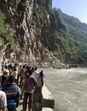 People watching the landslide on the Mandi-Kullu highway on Saturday morning.(HT Photo)