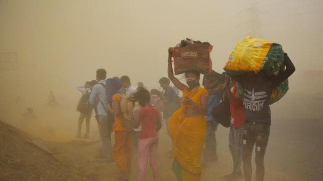 Migrant workers walking towards Farrukhabad and Sultanpur pause during a sudden dust storm, along NH24 near Indirapuram in New Delhi on May 10, 2020.(Ajay Aggarwal /HT PHOTO)