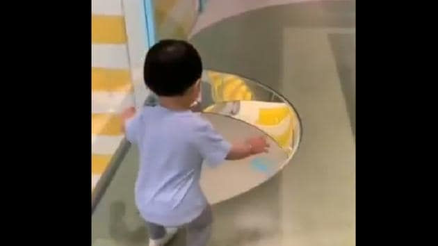 The image shows the kid stopping in front of the see-through floor.(Twitter/@RexChapman)