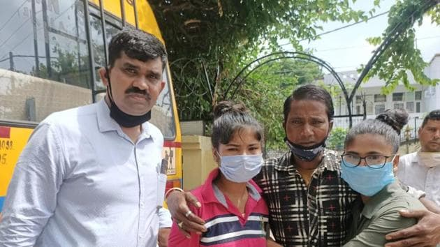 Assistant sub-inspector Rajesh Kumar from Panchkula's Anti Human Trafficking Unit (left) and two girls who reunited with their father after six years on Sunday.(HT Photo)