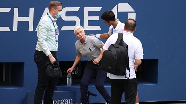 Novak Djokovic of Serbia tends to a lineswoman after inadvertently striking her with a ball hit in frustration(Getty Images)