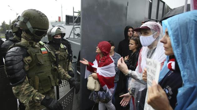 Belarusian opposition supporters try to speak to riot policemen as they gather in front of a police line toward the Independence Palace, residence of the President Alexander Lukashenko, in Minsk, Belarus.(AP)