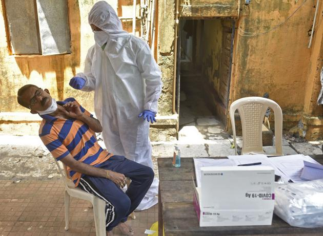 A healthcare worker collects swab sample of the resident at Goregaon in Mumbai. India's Covid-19 tally is now at 4,204,613 and 71,642 people have died so far.(Pratik Chorge/HT Photo)