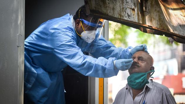 A health worker in PPE coveralls collects a swab sample from a man to test for Covid-19 in New Delhi.(Sanchit Khanna/HT Photo)