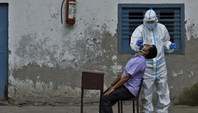 New Delhi, India - August 07, 2020: A health worker in PPE coveralls collects a nasal swab sample from a man to test for coronavirus infection, at Ramjas School, in Daryaganj, New Delhi, India, on Friday, August 07, 2020. (Photo by Biplov Bhuyan/ Hindustan Times)(Biplov Bhuyan/HT PHOTO)