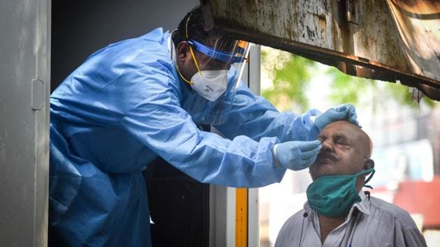 A health worker in PPE coveralls collects a swab sample from a man to test for Covid-19 at Hari Nagar in New Delhi.(Sanchit Khanna/HT PHOTO)