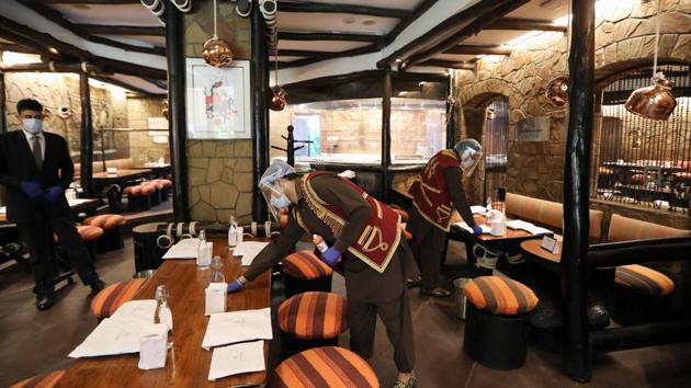 Employees wearing protective masks and face shields clean inside the Bukhara Restaurant at the ITC Maurya Sheraton Hotel in Delhi.(Bloomberg)
