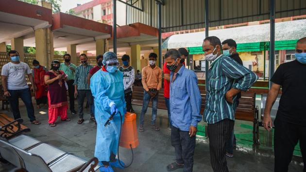 A worker in PPE sprays disinfectant to sanitise an area while people wait their turns to give samples for coronavirus testing, in New Delhi's Defence Colony area on Wednesday.(Amal KS/HT Photo)