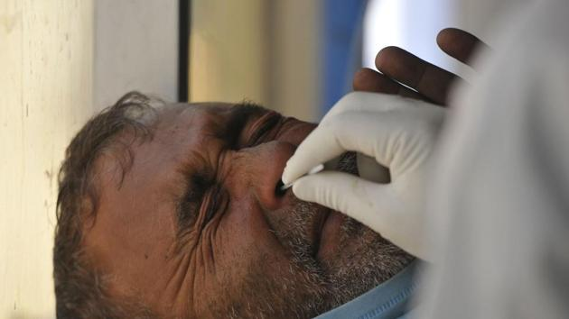 A paramedic taking a nasal swab sample in Srinagar.(HT File)