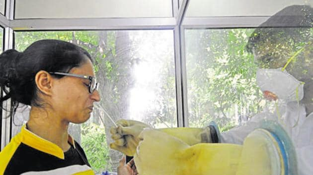 A health worker collects swab samples for coronavirus test in Noida.(Sunil Ghosh / HT Photo)