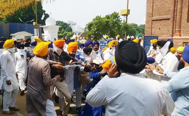 Shiromani Gurdwara Parbandhak Committee task force members using force to disperse Sikh protesters demanding action against culprits of the missing Guru Granth Sahib saroops outside Teja Singh Samundri Hall, the SGPC headquarters, in Golden Temple complex in Amritsar on Tuesday.(HT Photo)