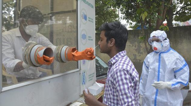 A health worker collects swab sample for coronavirus test in Ghaziabad on Tuesday.(Sakib Ali/HT Photo)