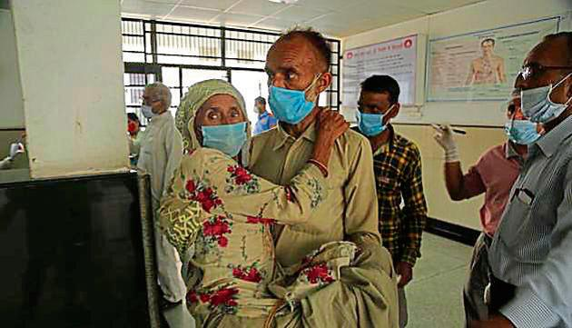 A man carries a woman to have her Covid-19 test done at a government hospital in Jammu on Tuesday.(AP)
