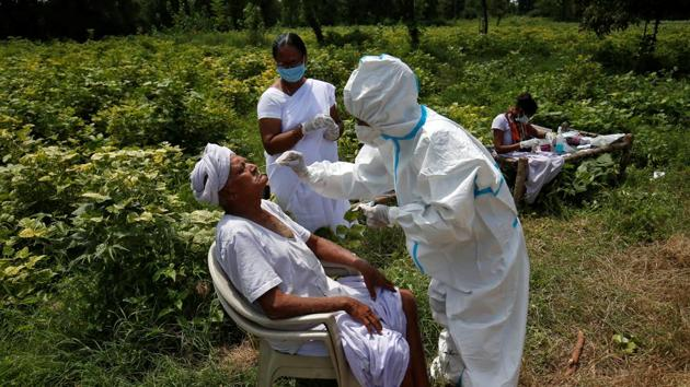 A healthcare worker wearing personal protective equipment (PPE) takes swabs from a farmer in a field, amidst the coronavirus disease (Covid-19) outbreak in Gujarat.(REUTERS)
