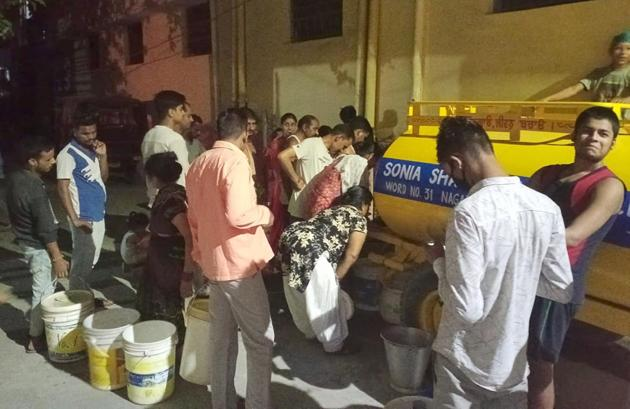 Residents queuing up to collect water from a tanker at Ward number 31 in Ludhiana on Saturday.(HT Photo)