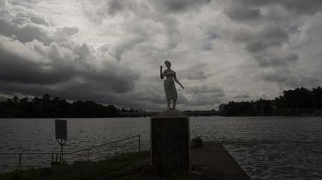 Rain clouds are seen behind a statue on the banks of the Periyar river in Kochi in Kerala.(AP PHOTO.)