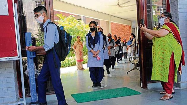 Masks, social distancing, sanitisers and videography — all precautions in place as students return to a government school in Sector 45, Chandigarh, on Monday.(Keshav Singh/HT)