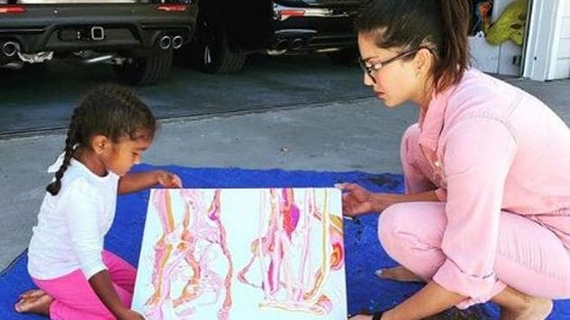Sunny Leone poses with daughter Nisha and their painting.