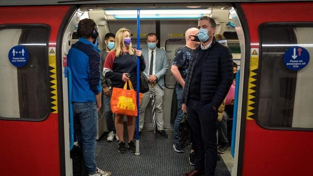 Commuters wearing face masks or covering due to the Covid-19 pandemic, stand aboard a Victoria Line London underground tube train as they travel during the evening 'rush hour' in central London on September 23.(AFP)