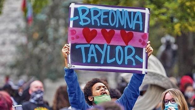 A protester holds up a sign after a grand jury announced its decision in the case of Breonna Taylor's death , in Louisville, Kentucky.