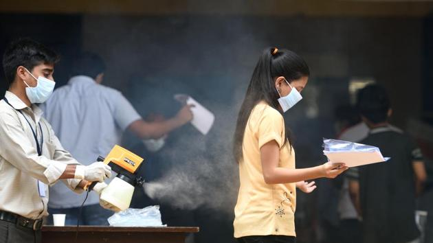 College staff sanitize a students before entering the exam center(Satish Bate/HT PHOTO)