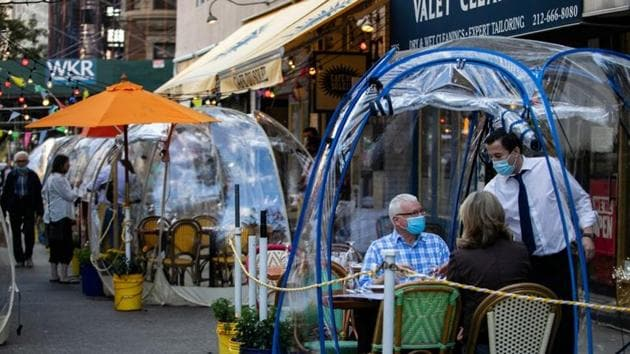 People sit outside Cafe Du Soliel under bubble tents following the outbreak of the coronavirus disease (Covid-19) in the Manhattan borough of New York City, US.(REUTERS)